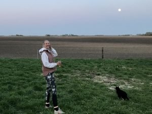 Annie stands next to a cat and a full moon.