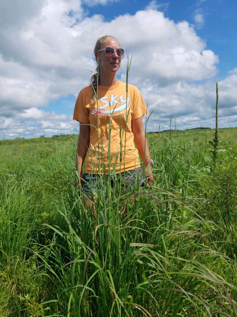 Annie standing next to big bluestem grass and wild golden rod.