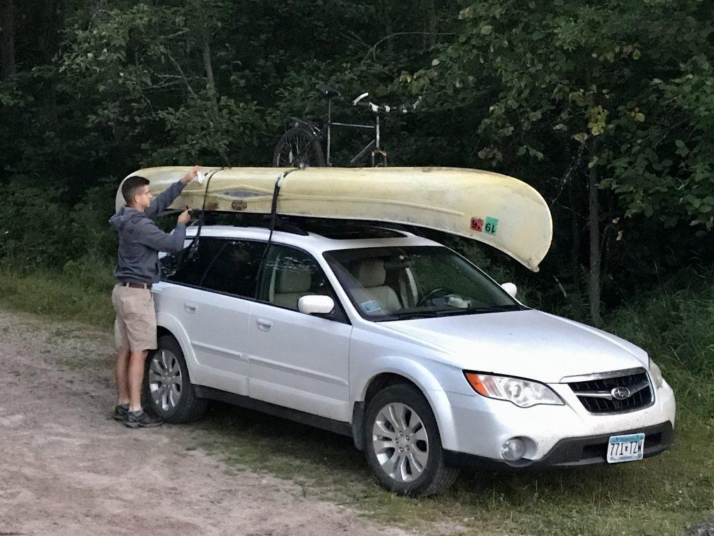 Nick strapping a canoe to the Subaru Outback.