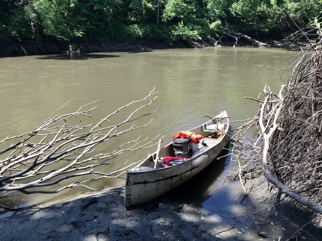Aluminum canoe sits full of items along river shore.