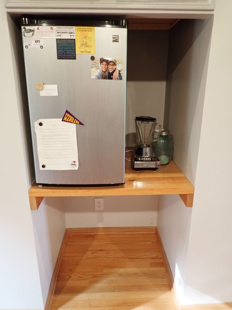 Annie and Nick's dorm fridge stands on a shelf in the place where a full sized fridge would sit. Counter leaves room for a blender.