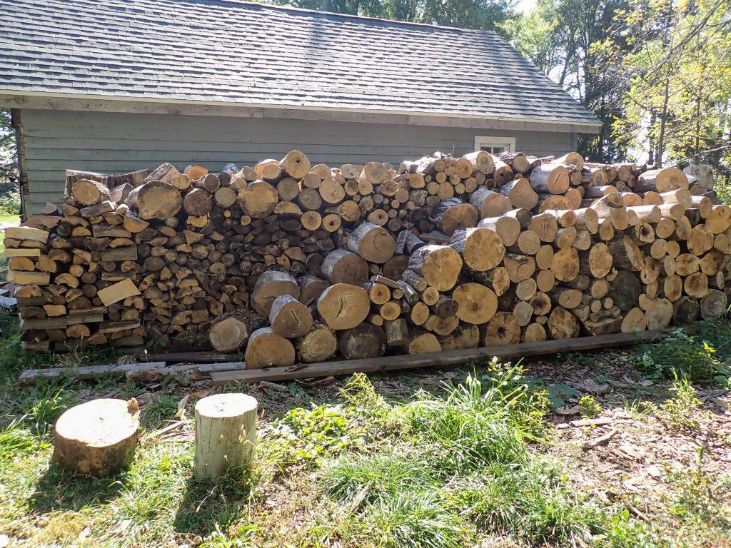 Large pile of firewood stacked up with garage in background.