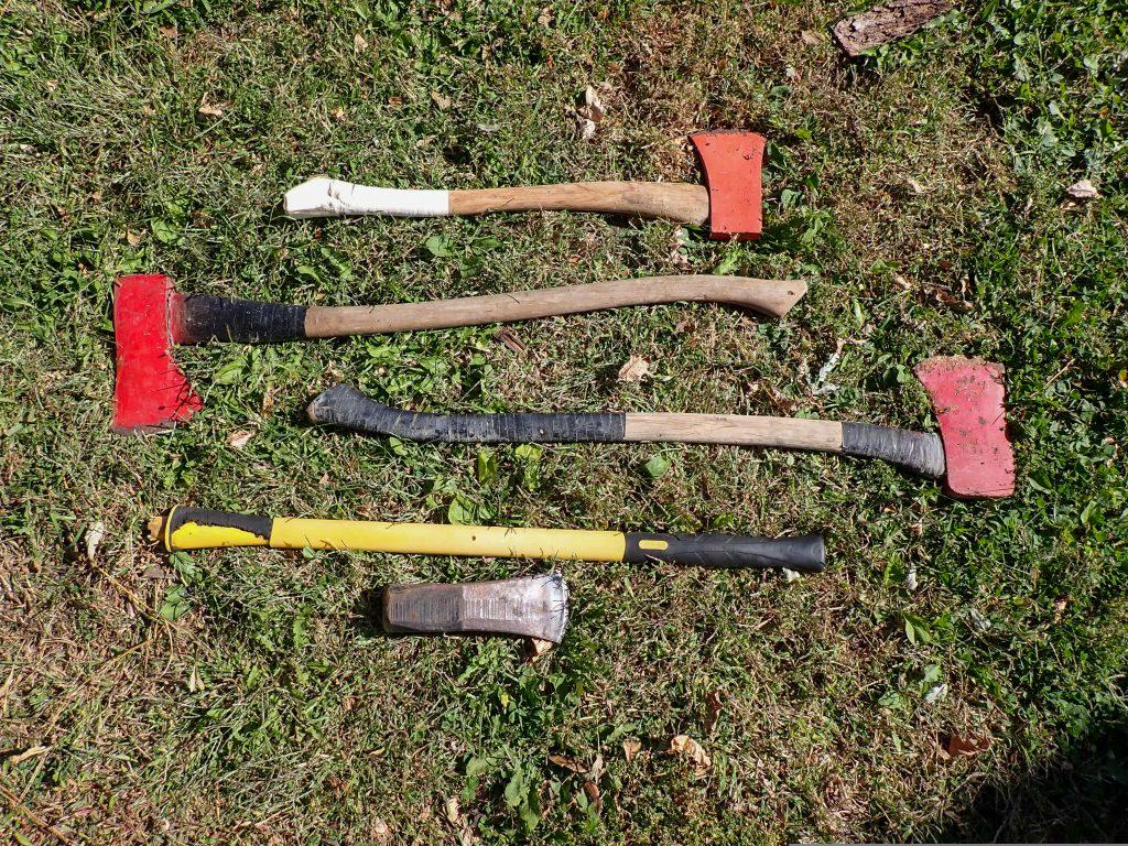 Multiple axes, variety of sizes and handles laying in the grass.