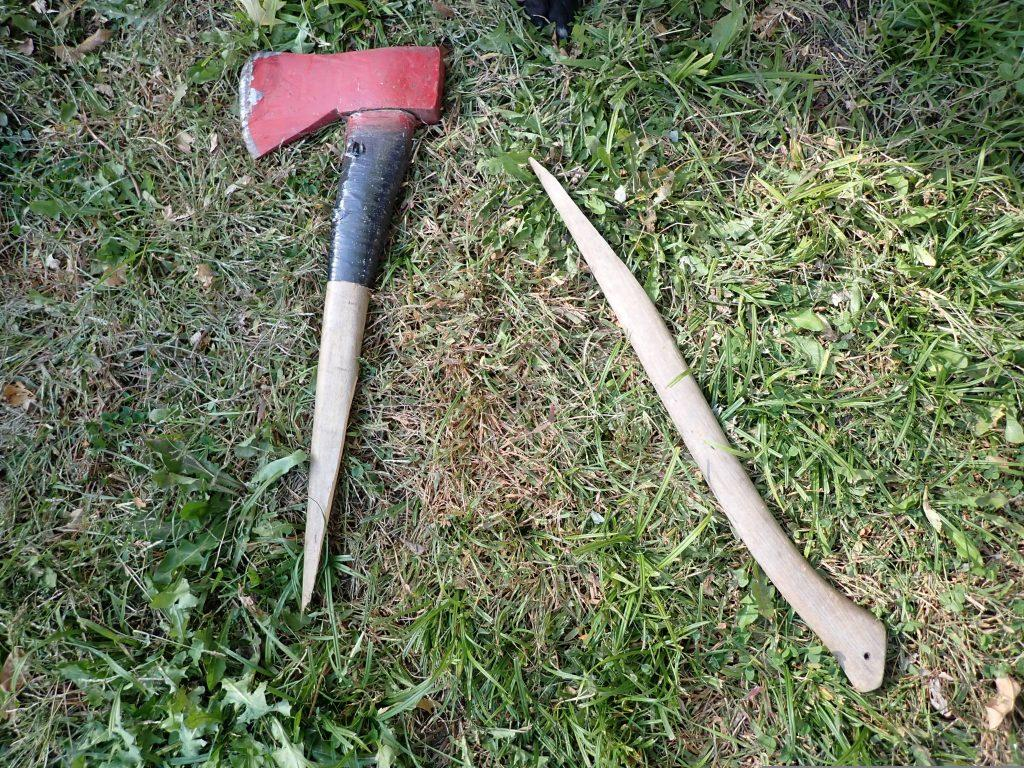The wooden handle on the axe lays broken in the grass.