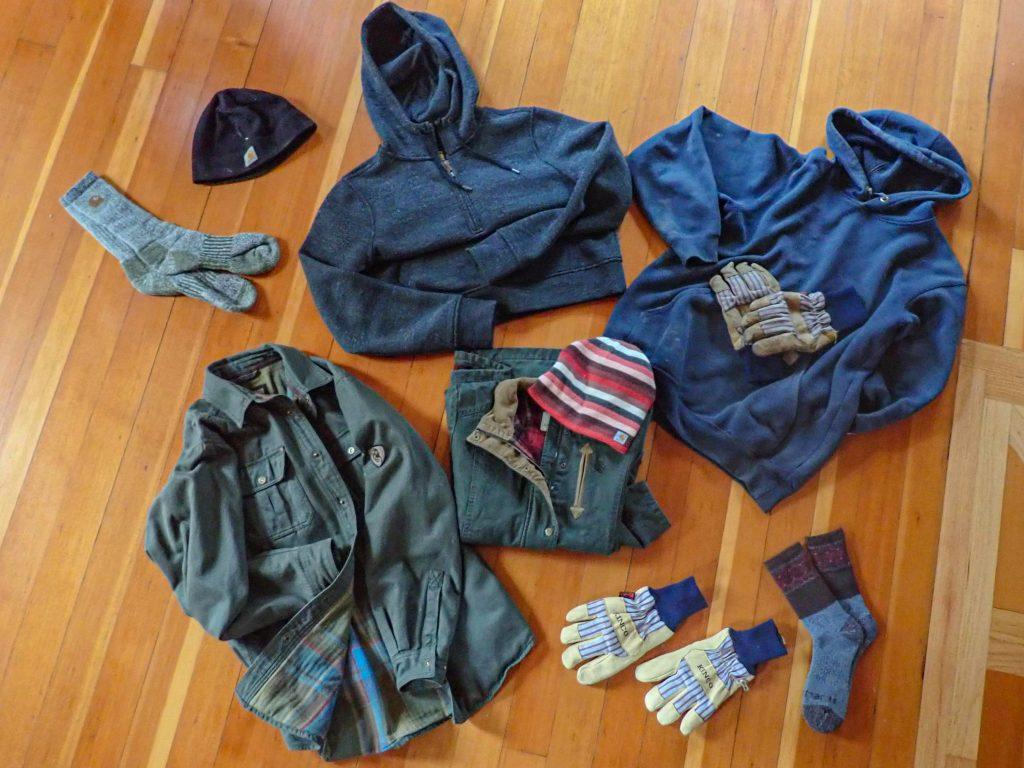 Flatlay of rugged clothes: 2 hats, 2 green jackets, 2 sets of socks, 2 sets of Kinco gloves, 2 sweatshirts.