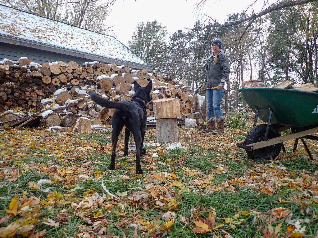Annie stands in front of log pile splitting firewood and Luna photo bombs. She's wearing an example of rugged clothes, the green jacket she steals from Nick.