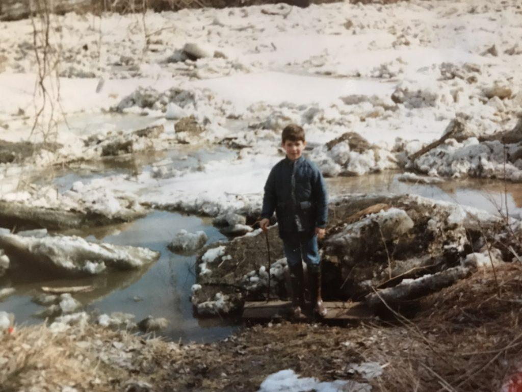 8-year-old Nick stands along a frozen river with his rubber boots and walking stick.