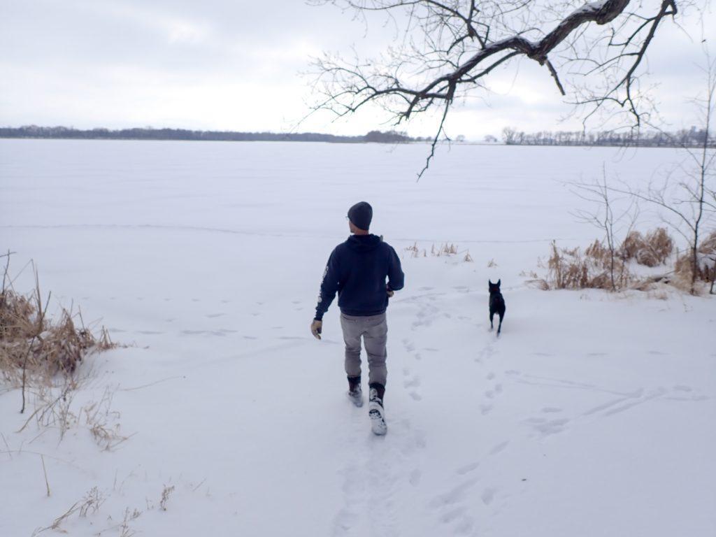 Nick walks through snow with Luna onto a frozen lake.
