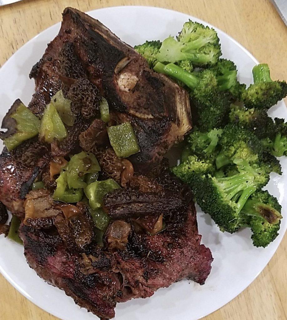Grass-fed t-bone steak served next to a pile of green broccoli.