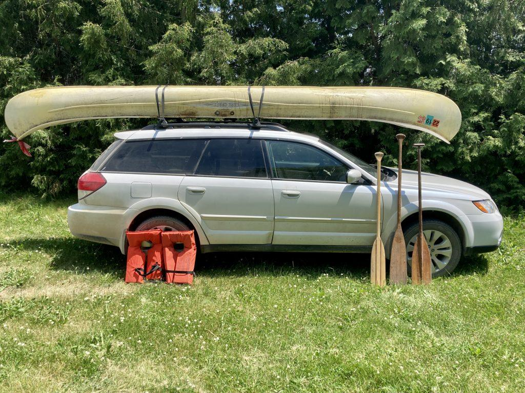 Fiberglass canoe sits atop our Subaru. Paddles and life jackets in front of it.